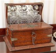 Sale 9058H - Lot 76 - An Edwardian oak three bottle tantalus with three glasses and a drawer (stuck)