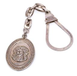 Sale 9177 - Lot 391 - AN EGYPTIAN SILVER RELIGIOUS KEY RING; oval fob depicting Jesus, length 137mm, width 27mm, wt. 17.74g.
