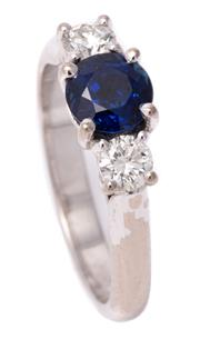 Sale 8980J - Lot 48 - An 18ct White Gold Sapphire and Diamond Ring; bead claw set with a round cut Royal blue sapphire of 1.05ct adjacent to 2 round brill...