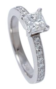 Sale 8980J - Lot 49 - An 18ct White Gold Diamond Ring; bead claw set with a Pincess cut diamond 0.75 G/SI1above shoulders set with 16 round brilliant cut...