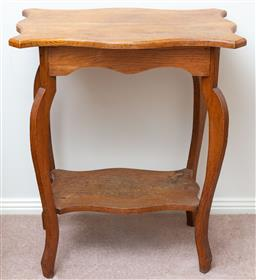 Sale 9103M - Lot 708 - An oak two tiered occasional table, the shaped top over outswept legs. Height 76cm x Width 66cm x Depth 51cm