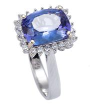 Sale 8928 - Lot 354 - AN 18CT WHITE GOLD TANZANITE AND DIAMOND RING; centring a cushion form chequerboard tanzanite of approx. 2.66ct surrounded by 22 rou...