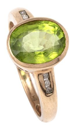 Sale 9124 - Lot 315 - A 9CT GOLD PERIDOT AND DIAMOND RING; rub set with an oval cut peridot of approx. 2.91ct to shoulders channel set with a total of 6 r...