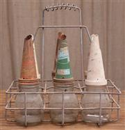 Sale 8984H - Lot 51 - A metal six bay oil basket containing six glass oil bottles with metal funnels. Various brands all 500ml. Height 40cm