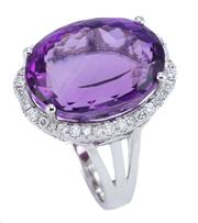 Sale 8928 - Lot 399 - AN 18CT WHITE GOLD AMETHYST AND DIAMOND COCKTAIL RING; featuring an approx. 15ct fancy oval cut amethyst surrounded by 36 round bril...