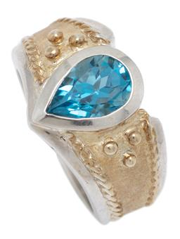 Sale 9221 - Lot 330 - A SILVER TOPAZ RING; 12mm wide ring with decorative gilt top rub set with a pear cut blue topaz of approx. 1.50ct, size L , wt. 11.68g.