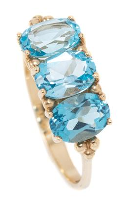 Sale 9160 - Lot 345 - A 9CT GOLD TOPAZ RING; bead claw set across the top with 3 oval cut blue topaz, size P, width 7mm, wt. 2.44g.