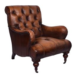 Sale 9245T - Lot 91 - A hand finished, top grain leather armchair, with folded leather surrounding deep Chesterfield buttoning, large rolled seat front an...