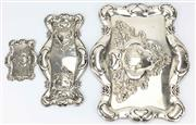 Sale 8269A - Lot 33 - Three matching Edwardian Secessionist sterling silver trays, with repousse flowers and stipple, and a cartouche with two storks in l...