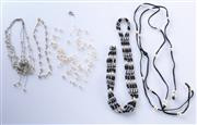 Sale 8550F - Lot 245 - Four assorted monochrome necklaces with pearl enhancements.