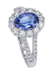 Sale 8928 - Lot 366 - A TANZANITE AND DIAMOND CLUSTER RING; centring an approx. 1.36ct oval cut tanzanite to surround and split shoulders set with 40 roun...