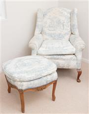 Sale 9066H - Lot 14 - An early C20th wingback armchair and foot stool on short cabriole legs upholstered in a French blue and white printed peasant scene.