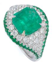 Sale 8991 - Lot 387 - AN 18CT WHITE GOLD EMERALD AND DIAMOND COCKTAIL RING; centring an approx. 4.4ct emerald cut emerald to dome surround and shoulders s...