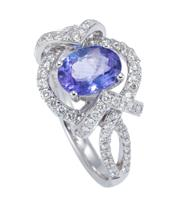 Sale 8928 - Lot 364 - AN 18CT WHITE GOLD TANZANITE AND DIAMOND RING; centring an approx. 1.21ct oval tanzanite to cross over bypass shoulders with applied...
