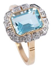 Sale 8974 - Lot 331 - A DECO STYLE TOPAZ AND DIAMOND RING; featuring a step cut light blue topaz to stepped border of round brilliant cut diamonds in 9ct...
