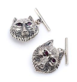 Sale 9194 - Lot 360 - A PAIR OF SILVER STONE SET WOLF CUFFLINKS; eyes set with round cut red garnets, size 20.5 x 16.5mm, wt. 11.59g.