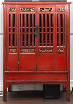 Sale 9160H - Lot 94 - A Chinese red and gilt lacquered raised food cabinet/ entertainment unit with bi fold doors opening to reveal shelved interior and f...