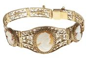 Sale 8641 - Lot 343 - A VINTAGE GOLD FILIGREE CAMEO BRACELET; central three links set with oval carved shell cameo portraits within wirework frames to box...