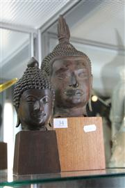 Sale 8195 - Lot 34 - Bronze Buddha Head on Timber Stand with a Smaller Example