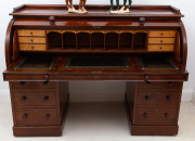 Sale 8677B - Lot 872 - A mahogany roll top desk with six pedestal drawers and the interior fitted with pigeon holes and six further drawers, the leather wr...