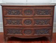 Sale 9081H - Lot 12 - An antique Italian oak three drawer curved commode with carved doors and raised on bracket feet.