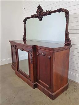 Sale 9179 - Lot 1073 - Victorian Mahogany Breakfront Sideboard, the arched mirror back carved with fruit & scrolls, above a central mirror panel door, flan...