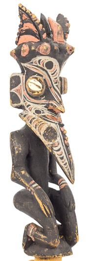 Sale 8269A - Lot 57 - A New Guinea Kamanibit stopper, consisting of a kneeling man with a pointed jaw and cowrie shell eyes, L 28cm PROV: New Guinea Arts