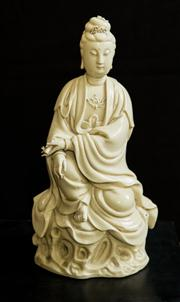 Sale 8439A - Lot 56 - A blanc de Chine Guanyin figure in the Ming period style,  seated on stand and holding a scroll, H 31cm