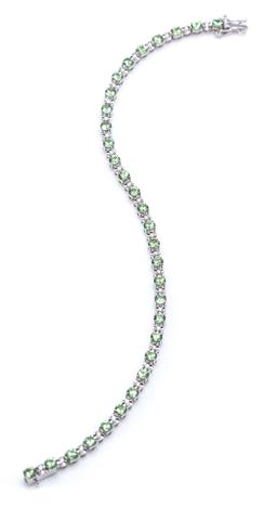 Sale 9194 - Lot 512 - AN 18CT WHITE GOLD DIAMOND AND GREEN GARNET BRACELET; claw set with 30 round brilliant cut diamonds totalling approx. 0.30ct between...