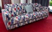 Sale 8677B - Lot 843 - A three seater sofa with red white and blue geometric design and cushions Height of back 65cm  L x 230cm, D x 90cm