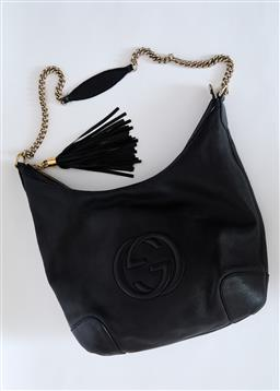 Sale 9095F - Lot 23 - A Gucci black leather handbag with gold coloured faded chain and black tassel, height 32cm.
