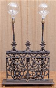 Sale 8984H - Lot 13 - A Wombat hollow lamp, the base featuring a segment of cast iron balustrade, raised over metal base and twin risers holding rounded b...