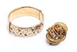 Sale 9253J - Lot 352 - A GOLD PLATED BANGLE AND STONE SET LOVE KNOT BROOCH; 19mm wide hinged hollow bangle with engraved front stamped 1/5 9ct Metal Core,...