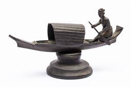 Sale 9170H - Lot 69 - A small metal figural group of man rowing a boat, raised on timber socle base, Length 17.5cm