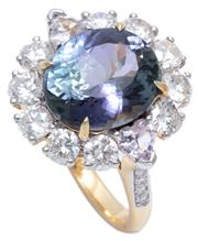 Sale 8982 - Lot 380 - A TANZANITE AND DIAMOND CLUSTER RING; centring on a 5.25ct oval cut tanzanite surrounded by 10 round brilliant cut diamonds, 2 heart...