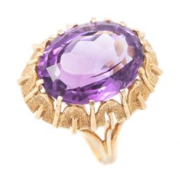 Sale 9177 - Lot 397 - AN 18CT GOLD AMETHYST COCKTAIL RING; cut down claw set with an approx. 9.00ct oval cut amethyst to a textured organic surround, size...