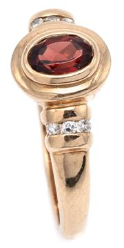 Sale 9090J - Lot 354 - A 9CT GOLD GARNET AND DIAMOND RING; rub set with an oval cut hessonite garnet to ribbed shoulders each channel set with 3 single cut...
