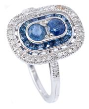 Sale 9054J - Lot 109 - A 14CT WHITE GOLD SAPPHIRE AND DIAMOND RING; two round cut blue sapphires to surround of mixed cut sapphires to border and shoulders...