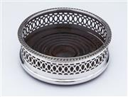 Sale 9080J - Lot 156 - A silverplate on copper bottle coaster with pierced body, the base fitted with a timber panel with concentric ring turnings. D: 11.5cm