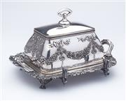 Sale 9080J - Lot 142 - An antique Meriden silverplate butter dish C: 1900, the lid embossed with bold bows and floral garlands, the base with a thick cryst...