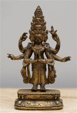 Sale 9160H - Lot 114 - A gilt bronze figure of Shiva with twelve heads and twelve arms, Height 18cm