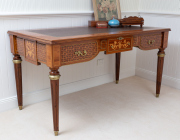 Sale 8677B - Lot 865 - A French Louis XVI style bureau plat with tooled leather top, marquetry and parquetry inlay on tapered legs the apron with three dra...