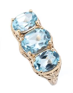 Sale 9221 - Lot 370 - A 9CT GOLD VICTORIAN STYLE TOPAZ RING; set across the top with 3 oval cut blue topaz to pierced scrolling gallery and shoulders, wid...