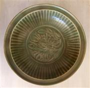 Sale 8259A - Lot 80 - A Chinese Celadon Shallow Dish, 	Ming Dynasty, modelled with a central raised figure in script , d 25cm