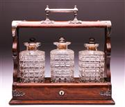 Sale 9081 - Lot 91 - Oak Tantalus with three cut glass decanters with silver on copper stoppers (H31cm x W37cm x D13cm)