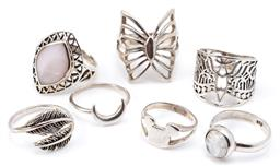 Sale 9132 - Lot 561 - SEVEN SILVER RINGS; two stone set with white labradorite and mother of pearl, others butterfly, bird, feathers, Micky Mouse and cres...