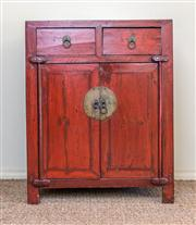 Sale 8259A - Lot 87 - A Chinese Red Lacquered Side Cabinet, modelled with a square top, leading to duel short drawers and panel doors, all on square turne...