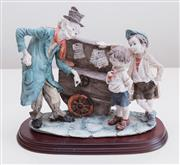 Sale 8369A - Lot 97 - A porcelain figural group of a barrel organ grinder and two young boys, H 25 x W 28cm