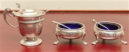 Sale 9098H - Lot 17 - A hallmarked sterling silver cruet set comprising a footed and lidded mustard, two salts with blue glass liners and three spoons, di...