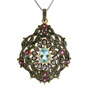 Sale 8060B - Lot 337 - A STERLING SILVER GILT GEM SET PENDANT; centring a pear shape blue topaz surrounded by rubies (treated) emeralds, rose and table cut...